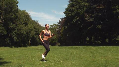 Sporty brunette running on grass Live Action