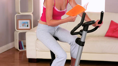 Sporty woman exercising on exercise bike at home Live Action