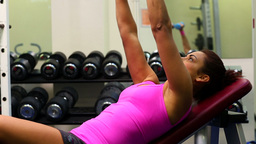 Sporty young woman lifting dumbbells Footage