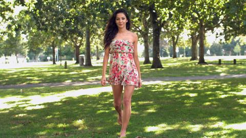 Gorgeous happy brunette walking in park Live Action