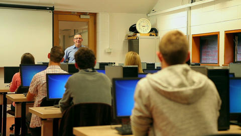 Students listening to lecturer in computer room Footage