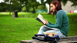 Pretty student sitting on bench reading a book lis Footage