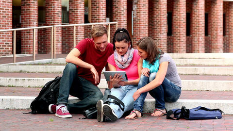 Happy students using tablet outside on steps Footage