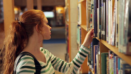 Focused student picking a book in the library Footage