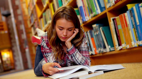 Student lying on floor reading book in the library Footage