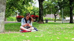 Student sitting on the grass making a phone call Footage