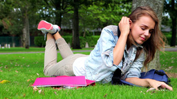 Tired student lying on the grass and answering her Footage
