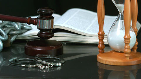 Gavel falling onto sounding block beside hourglass bible and handcuffs Footage