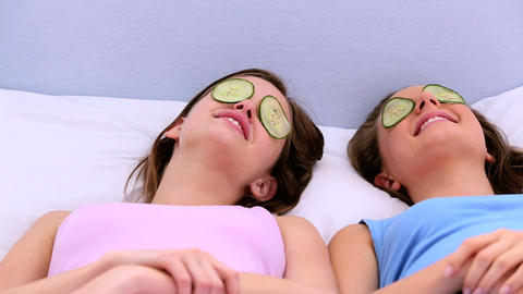 Girls lying on bed with cucumber over their eyes Footage