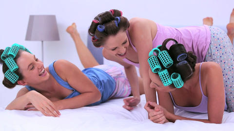 Girls in hair rollers lying in bed and chatting Footage
