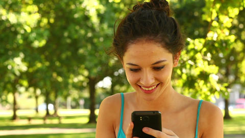 Gorgeous brunette sending a text in the park Footage