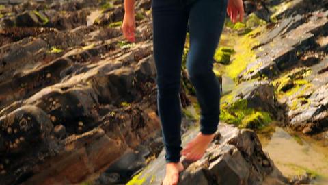 Beautiful brunette walking along rocks by the beac Footage