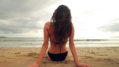 Brunette sitting on the beach facing the water Footage