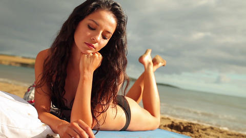 Happy brunette lying on the beach smiling at camer Footage