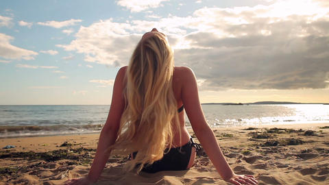 Blonde in bikini sitting on the beach facing the w Footage