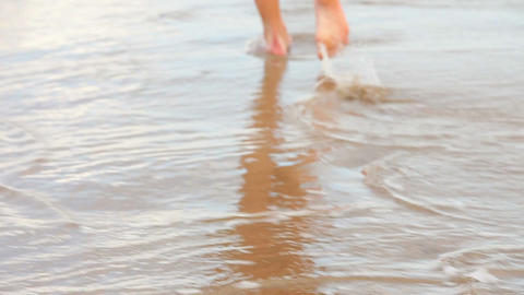 Womans feet walking on the wet sand along the tide Live Action