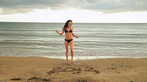 Gorgeous brunette dancing around with 2012 written in the sand Live Action