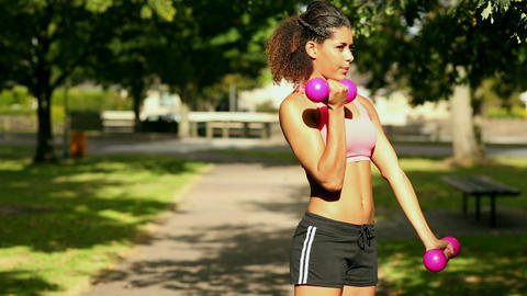 Content sporty woman lifting dumbbells Footage