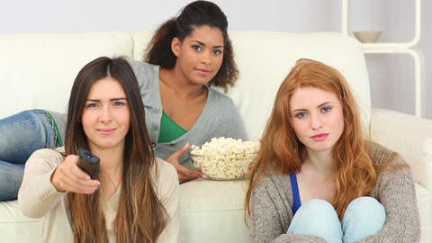 Young friends watching television eating popcorn Footage