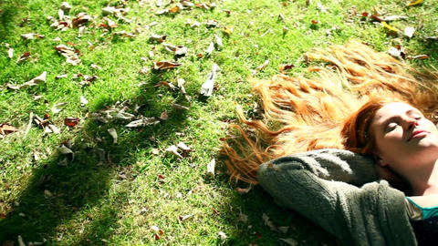 Beautiful redhead napping on lawn Live Action
