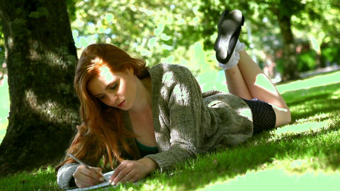 Young redhead lying on lawn while doing assignment Footage