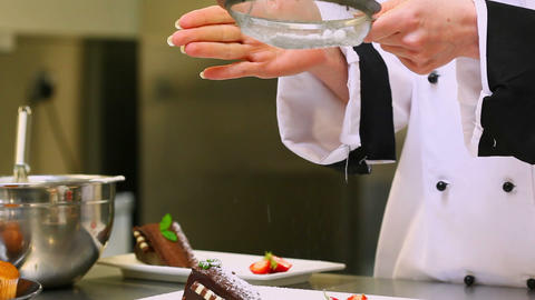 Chef sieving icing sugar over a dessert Footage