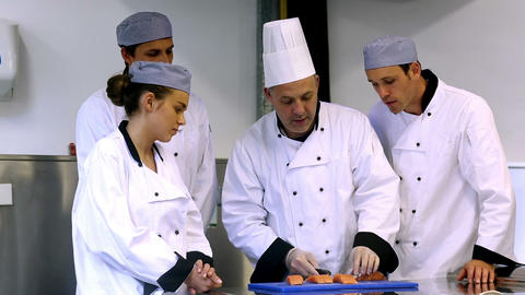Head chef showing his trainees how to fillet a sal Footage
