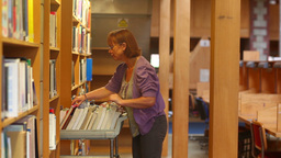 Librarian pushing trolley through the library returning books Footage