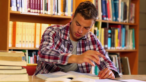 Concentrating student studying in the library Footage