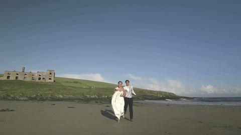 Smiling newlyweds running to the camera on the beach Live Action