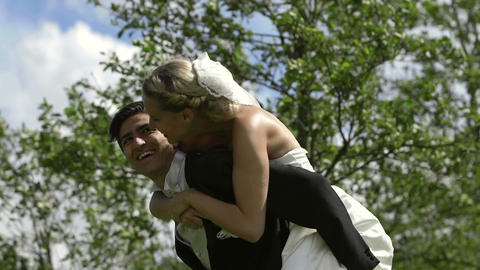 Groom giving his pretty wife a piggy back Footage