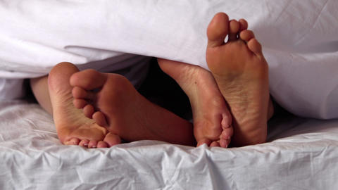 Couples feet wiggling under the blanket Footage