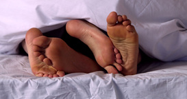 Couples feet wiggling under the duvet Footage