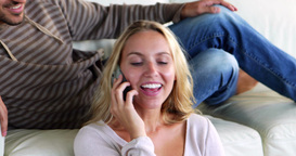 Happy young couple sitting on the couch while girl Footage