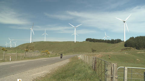 motorbike passes wind turbines Stock Video Footage