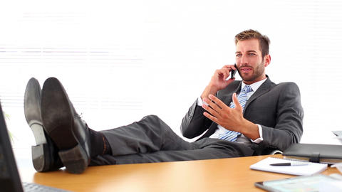 Relaxed businessman putting his feet up talking on Footage