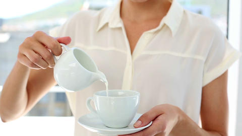 Pretty businesswoman pouring milk into cup Footage