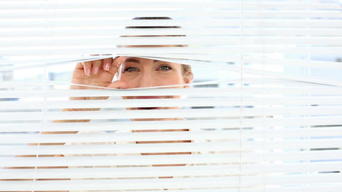 Smiling businesswoman peeking through the blinds Footage
