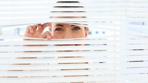 Surprised businesswoman peeking through the blinds Live Action