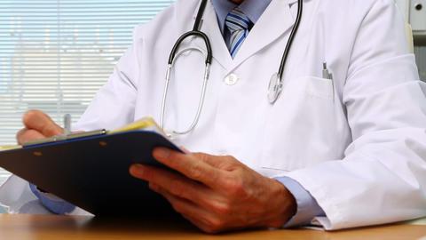 Doctor writing on clipboard ライブ動画