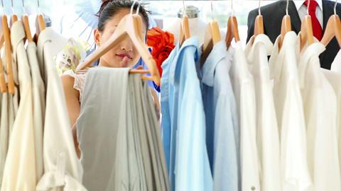 Pretty fashion designer looking through her clothing rail Footage
