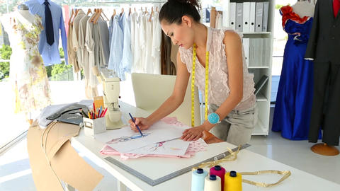 Fashion designer sketching a design at table Footage