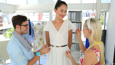 Designers Adjusting Dress On Model While Chatting stock footage