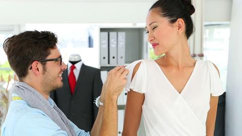 Designer adjusting sleeve of dress on model Footage