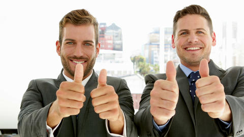 Smiling businessmen looking at camera giving thumbs up Footage