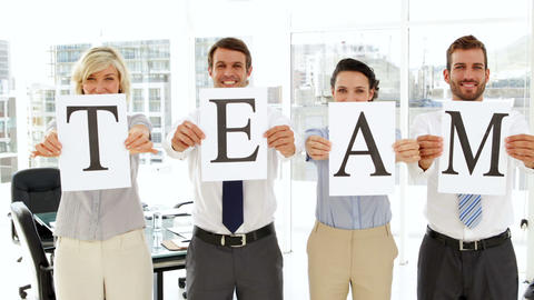 Business people holding up pages spelling out team Footage