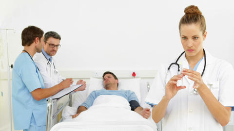 Doctors speaking with sick patient in bed while nurse prepares injection Footage
