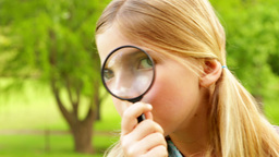 Cute little girl using magnifying glass in park Footage