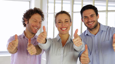 Gleeful colleagues showing thumbs up to camera Footage