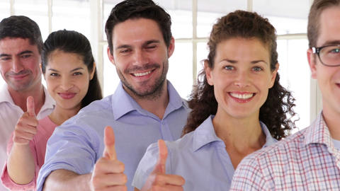 Attractive designer standing in a row showing thumbs up Stock Video Footage